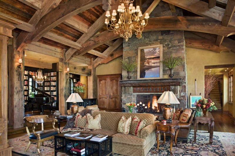 The living room has a large stone mosaic fireplace across from the sofas topped with a large golden chandelier hanging from a tall wooden cathedral ceiling with exposed beams.