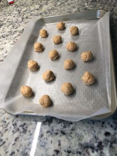 The peanut butter balls are placed on a baking sheet.