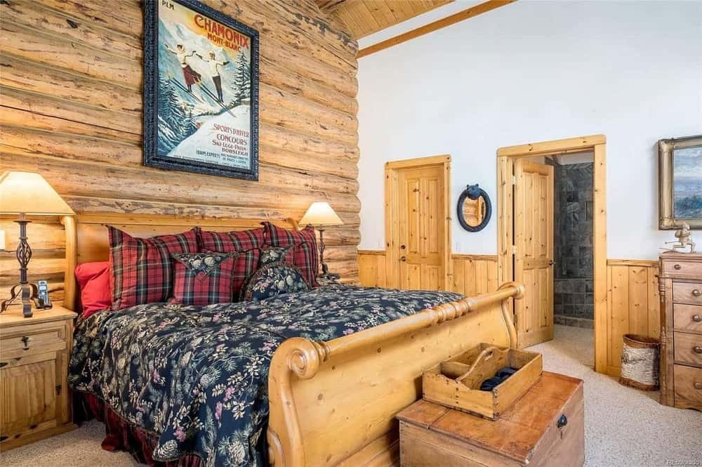 The bedroom has a tall log beam wall behind the headboard of the large wooden sleigh bed topped with a colorful wall-mounted artwork.