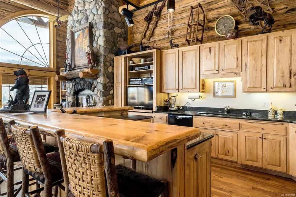 This is the rustic kitchen with wooden cabinetry that matches the tone of the hardwood flooring and log beam walls. This is paired with an L-shaped kitchen island that has a breakfast bar.