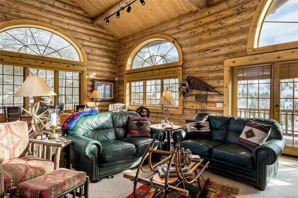 This is a close look at the living room showcasing the green leather sofas across from the stone fireplace paired with a coffee table made out of a snow sled.