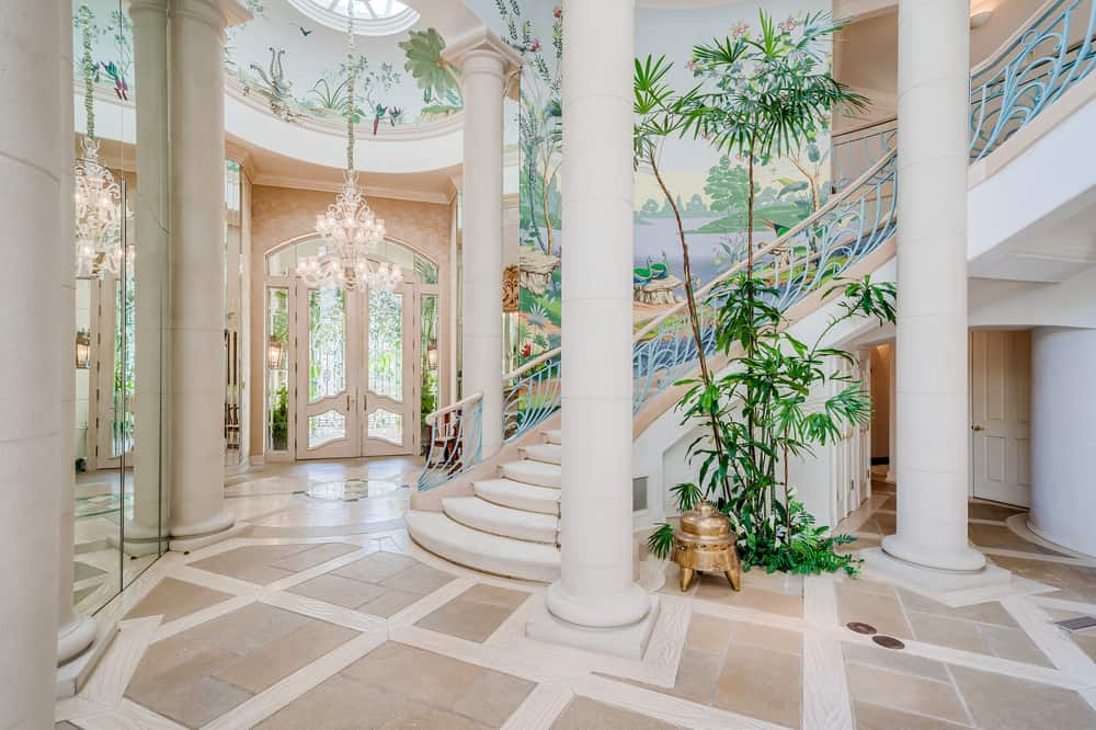This is a view of the mansion's staircase and foyer with a large two-story atrium that has white pillars, tall trees and colorful nature scenery on its wallpapers. Image courtesy of Toptenrealestatedeals.com.
