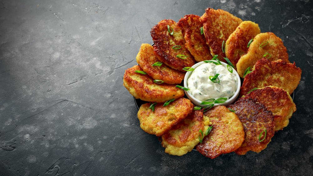 This is a platter of sausage hash brown cups with a dip in the middle.