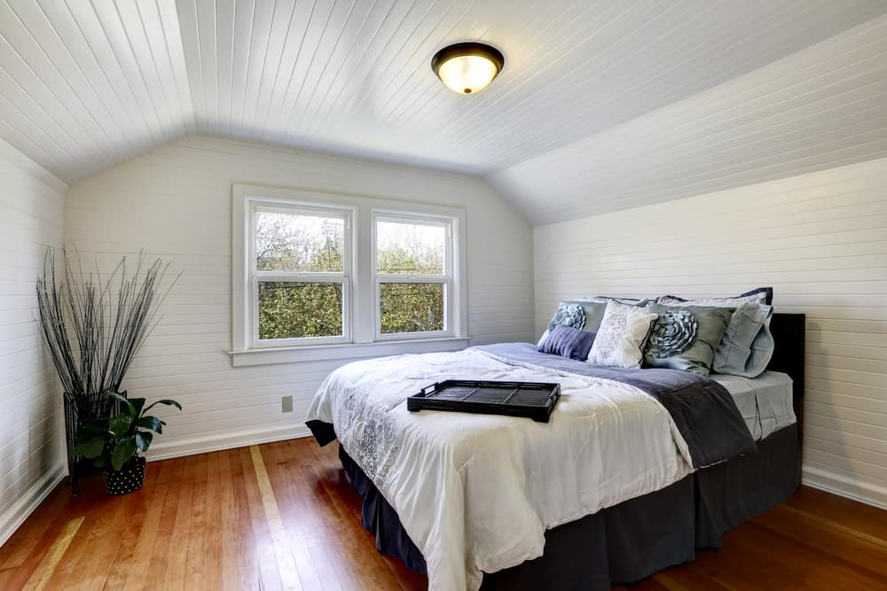 This bedroom has a large bed and potted plant that stand out against the surrounding white wooden shiplap walls and cove ceiling.