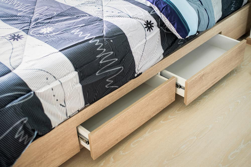 This is a close look at a wooden bedframe that has built-in drawers.