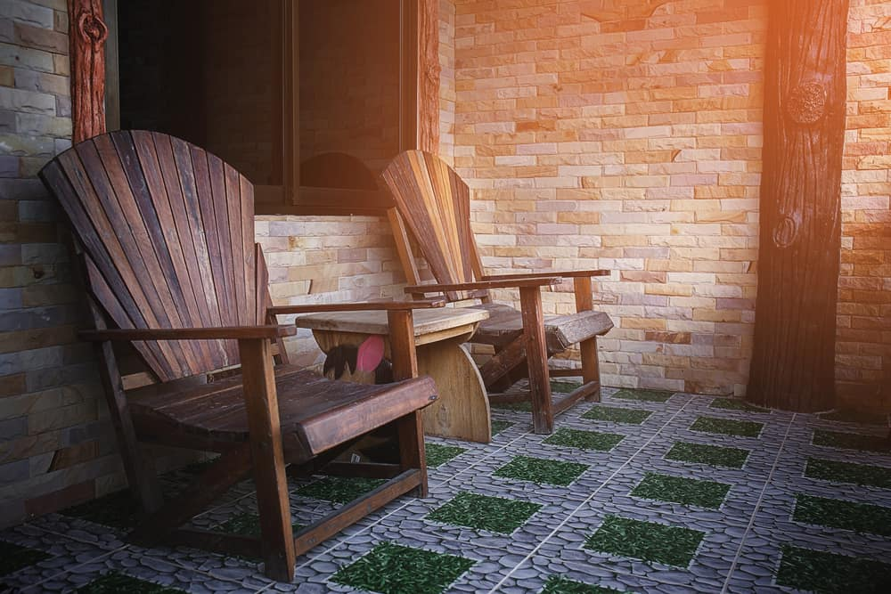 This is a balcony that has brick walls, wooden arm chairs and a wooden side table.