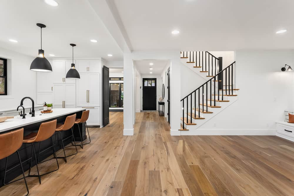 This is a look at the interior of the house that has bright white walls and ceiling complemented by the hardwood flooring.