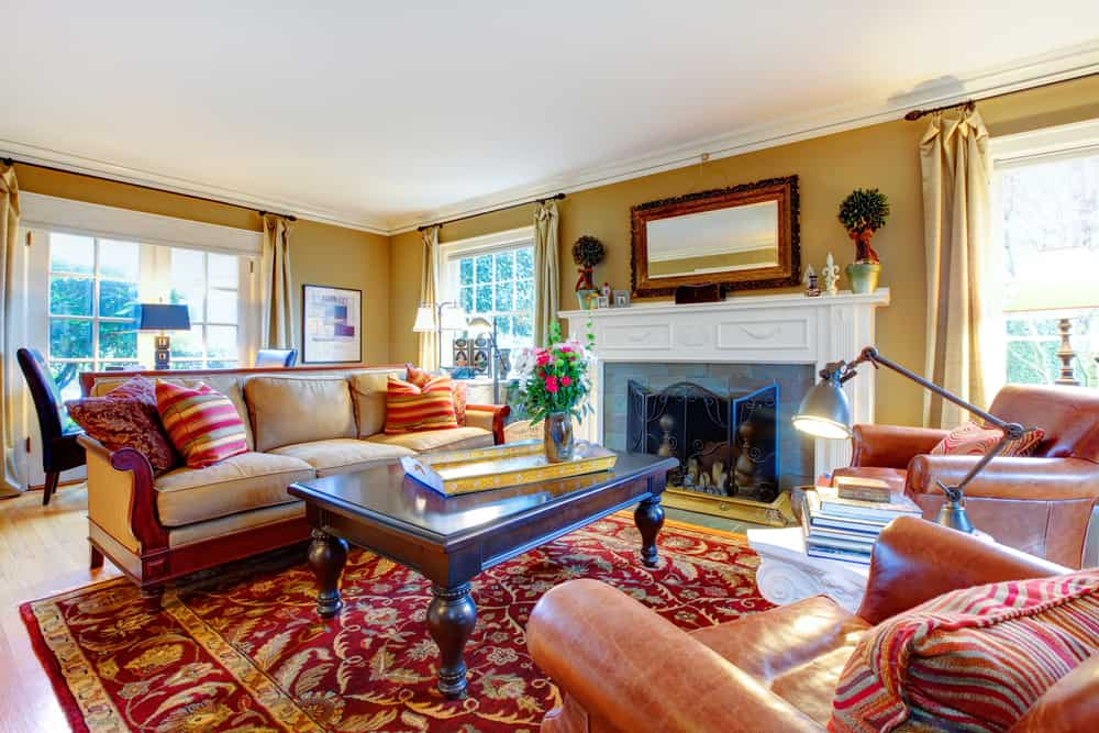 This is a cozy formal living room with a sofa set, a wooden coffee table and a patterned area rug across from the fireplace.