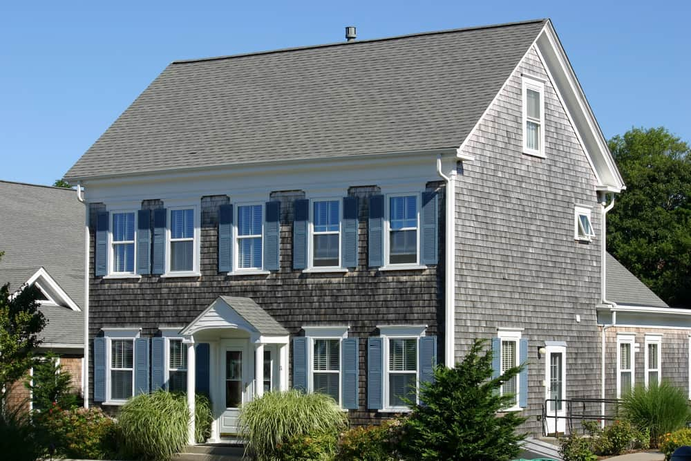 This is a full view of the shingle-style cape cod home with gray exterior walls accented by the white frames of the windows.