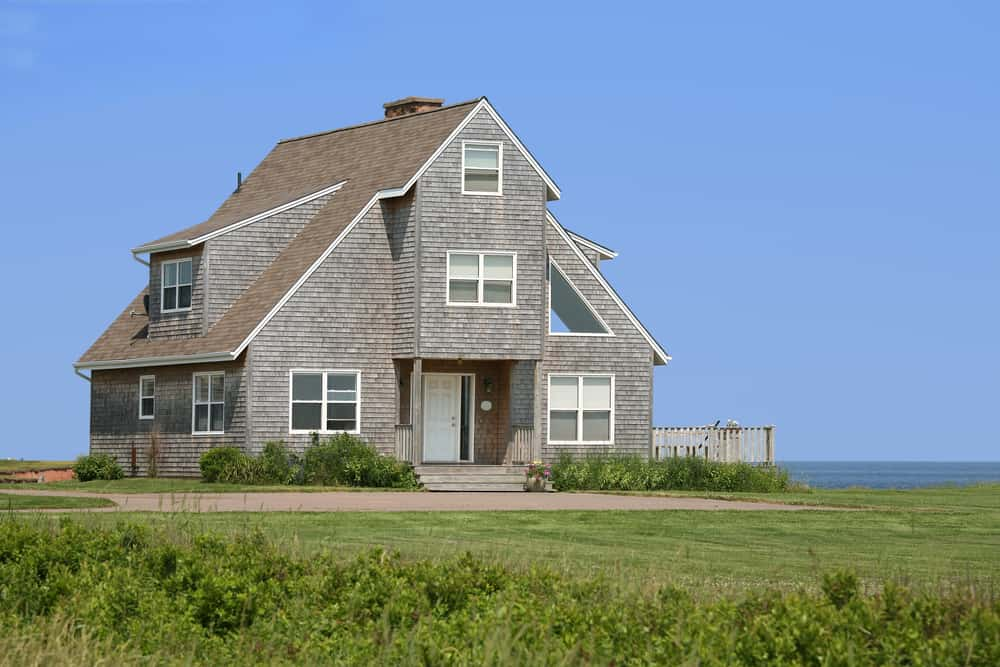 This is a full view of a large three-level shingle-style home with A-frame roof and large square windows.