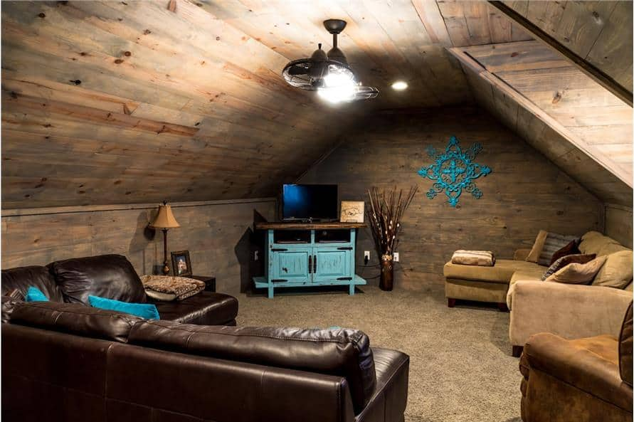 The bonus room is furnished with leather and fabric seats along with a blue distressed TV stand.