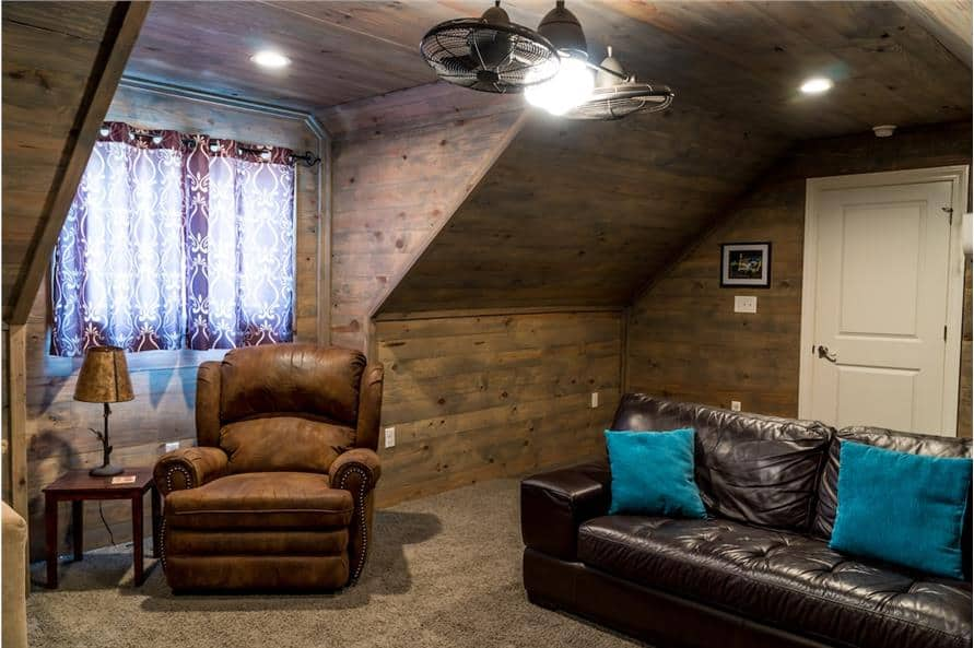 The bonus room includes carpet flooring, a vaulted ceiling, and a window dressed in pattered curtains.