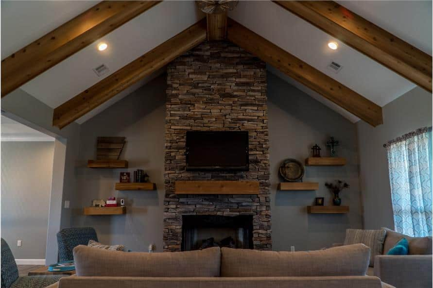 Great room with beige sofas, a stone fireplace, and a cathedral ceiling with exposed beams matching with the floating shelves.