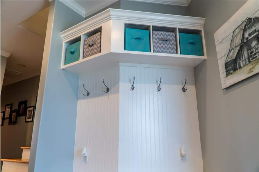 Kid's nook with white built-ins fitted with blue and chevron storage bins.
