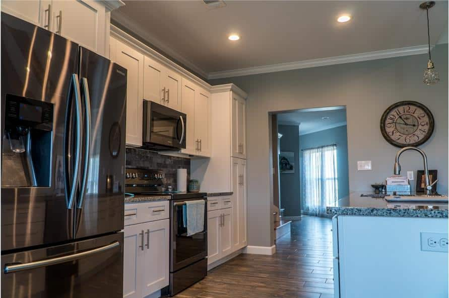 Kitchen with white cabinetry, stainless steel appliances, and a breakfast bar fitted with a sink.