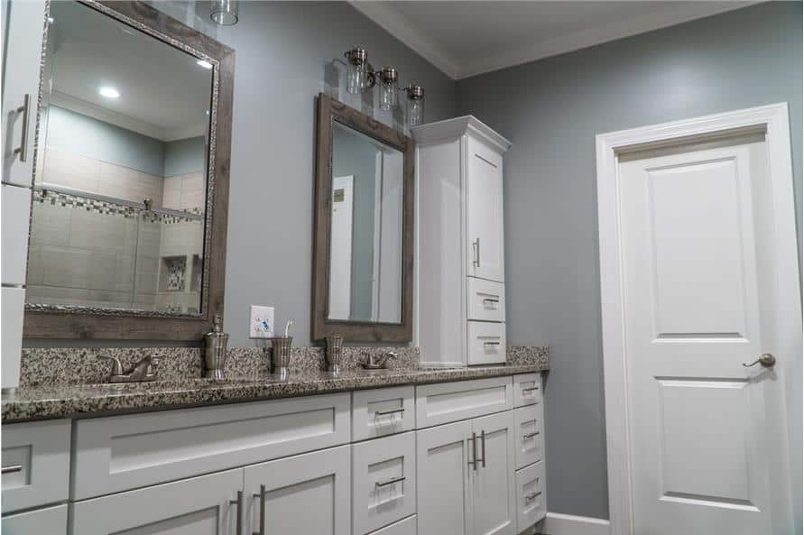 The primary bathroom has a dual sink vanity topped with a white cabinet and wooden framed mirrors.