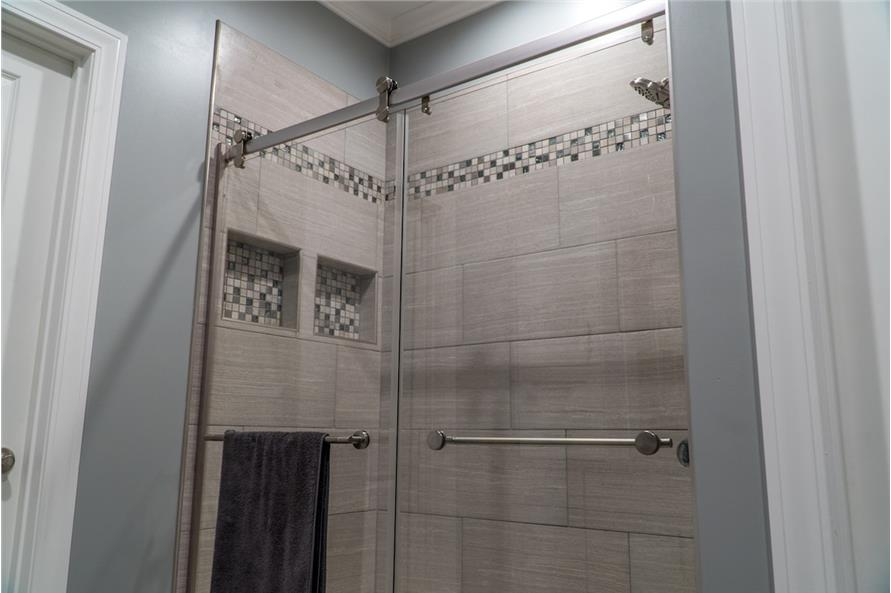 Walk-in shower with chrome fixtures, inset shelves, and glass doors.