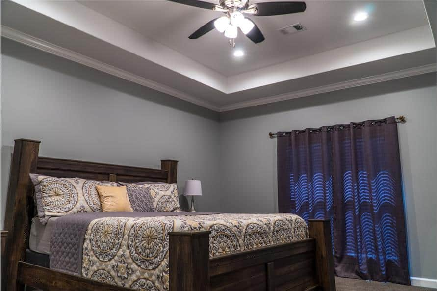 The primary bedroom features a dark wood bed and a tray ceiling mounted with a fan.