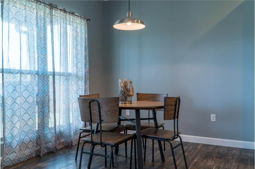 Breakfast nook with a large window and a round dining set illuminated with a dome pendant.