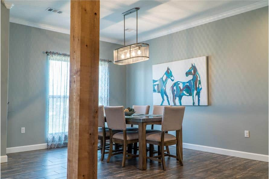 The formal dining room offers a wooden dining set, a linear chandelier, and a large artwork adorning the gray walls.