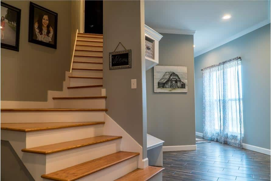 A wooden staircase adorned with portraits leads to the bonus room.