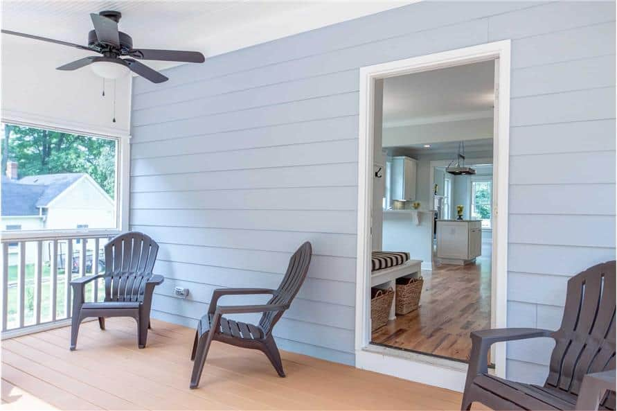 The screened porch includes a ceiling fan and wooden lounge chairs over wide plank flooring.