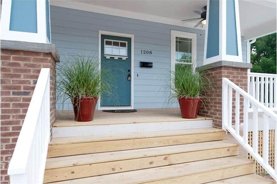 Covered front porch with a wooden stoop, tapered columns, and a blue entry door.