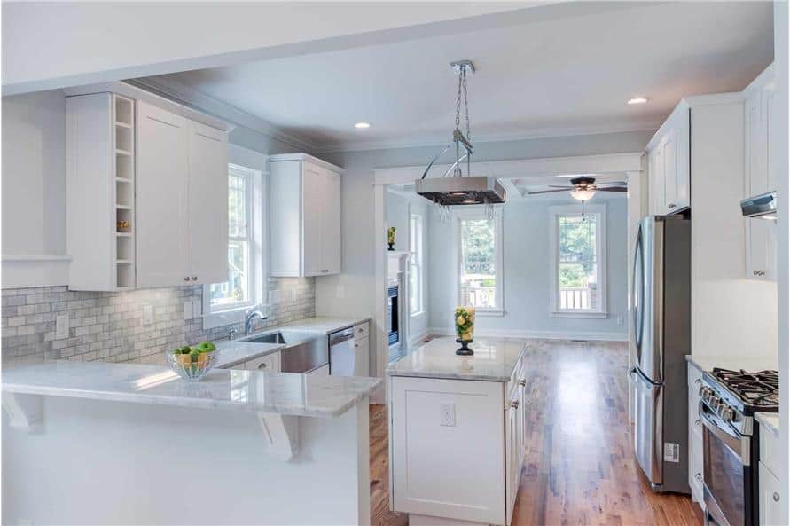 The kitchen is equipped with stainless steel appliances, white cabinetry, a center island, and a marble top snack bar.