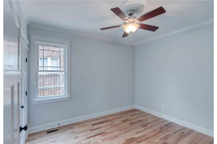 This bedroom offers a ceiling fan and hardwood flooring.
