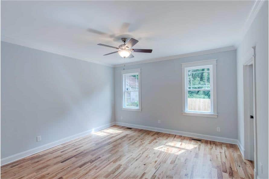 Primary bedroom with hardwood flooring, gray walls, and a couple of white-framed windows.
