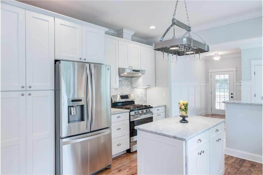 A stainless steel pot rack hangs over the center island.