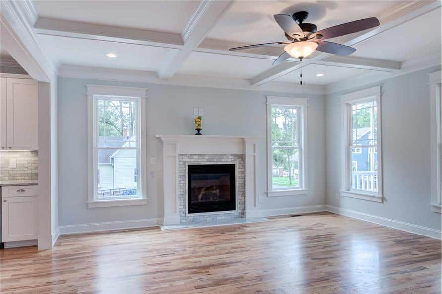 Great room with a coffered ceiling, hardwood flooring, and a fireplace flanked by windows.