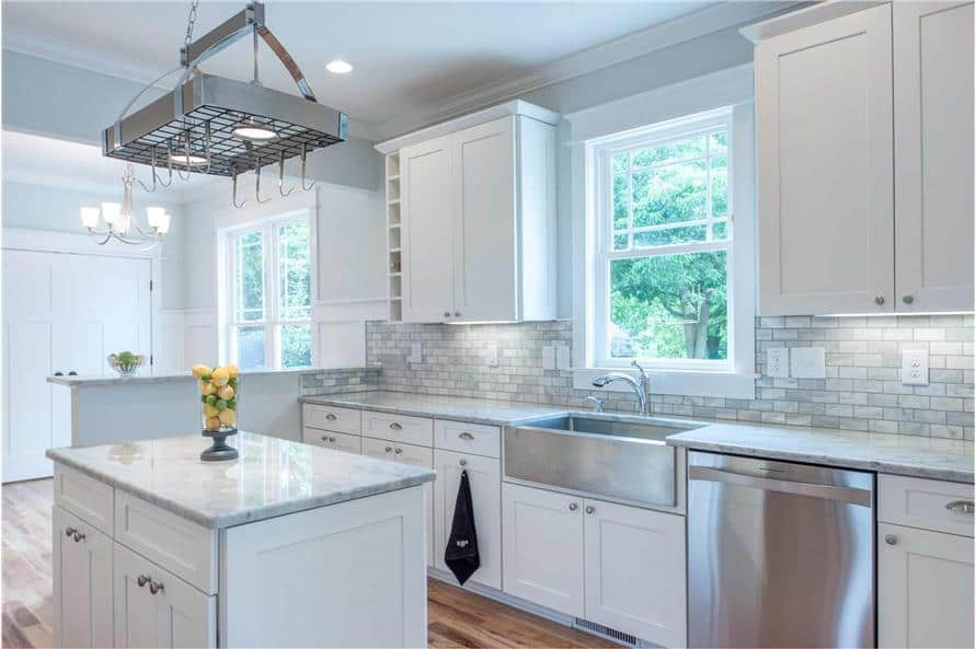 The kitchen includes a farmhouse sink and a white framed window that invites natural light in.