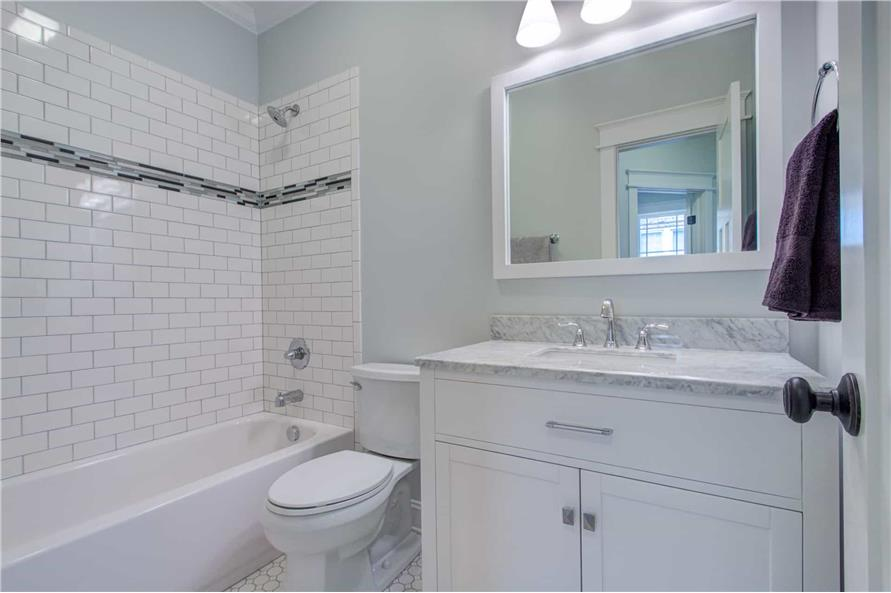 This bathroom is equipped with a single sink vanity, a toilet, and a tub and shower combo accentuated with a subway tile backsplash.