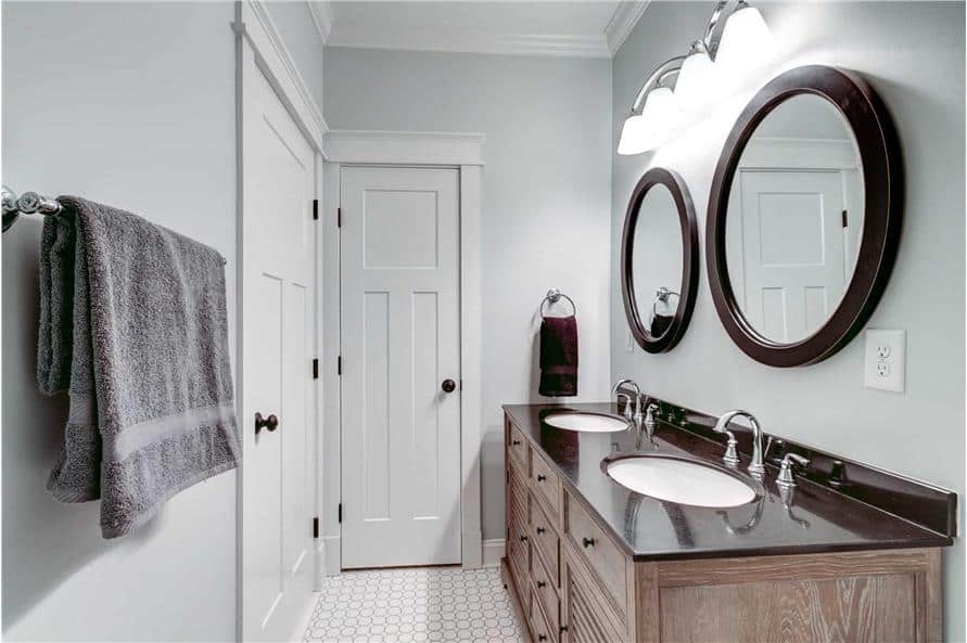 The primary bathroom features a wooden vanity with double sinks and round mirrors.