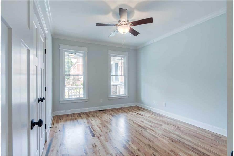 Third bedroom with white hardwood flooring, framed windows, and light gray walls lined with white moldings.