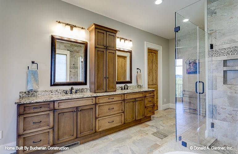 The primary bathroom has a large brown wooden structure that houses the two sinks along with built-in drawers and cabinets across from the glass-enclosed shower area.