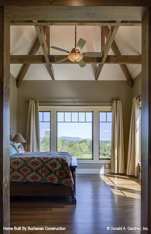 This is a look at the primary bedroom from the vantage of the wooden door. The bedroom is topped iwth a beamed cathedral ceiling that matches the wooden traditional bed brightened by the glass windows.