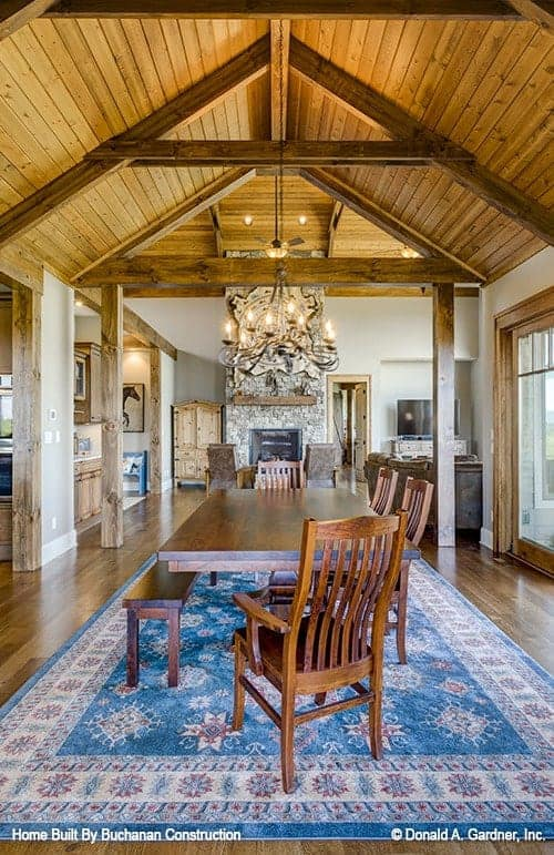 The simple dining area is a few steps from the living room with a view of the fireplace. It has a rectangular wooden dining table paired with a wooden bench and wooden chairs on a colorful patterned area rug.