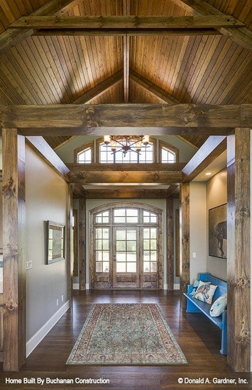 The mountain chalet-style foyer has a tall cathedral wooden ceiling with exposed beams and transom windows that match the main door with glass panels. On the side is a wooden built-in bench that stands out with its rustic blue tone.