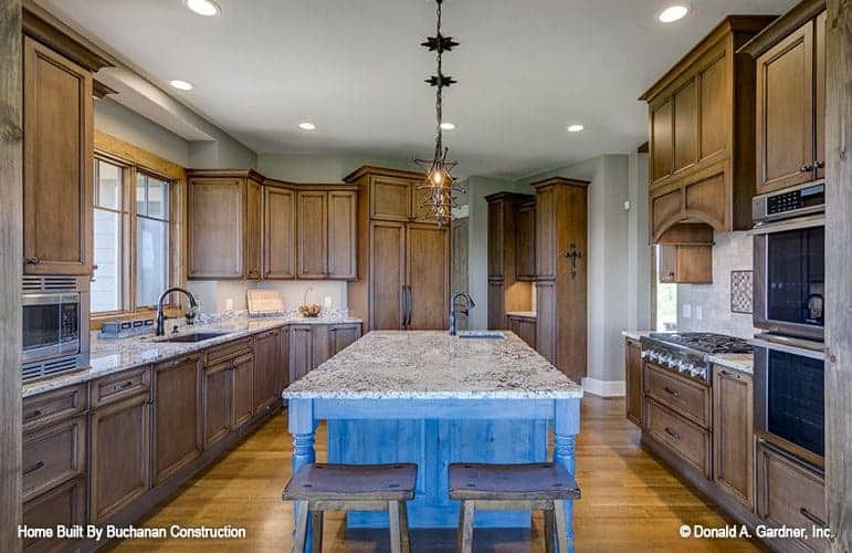 This is a close look at the kitchen with a large kitchen island in the middle of brown wooden cabinetry that makes the appliances stand out and matches well with the hardwood flooring.
