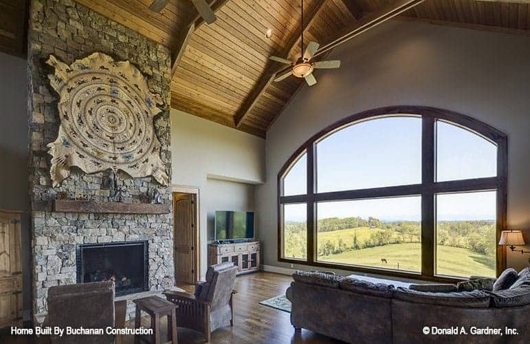 The spacious living room has a rustic stone fireplace on one side paired with a couple of armchairs along with a brown leather sofa facing the large arched window.