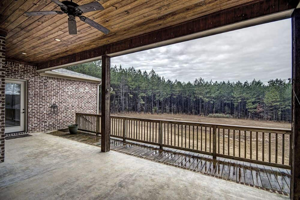 The covered porch overlooks the expansive yard and the forest beyond.