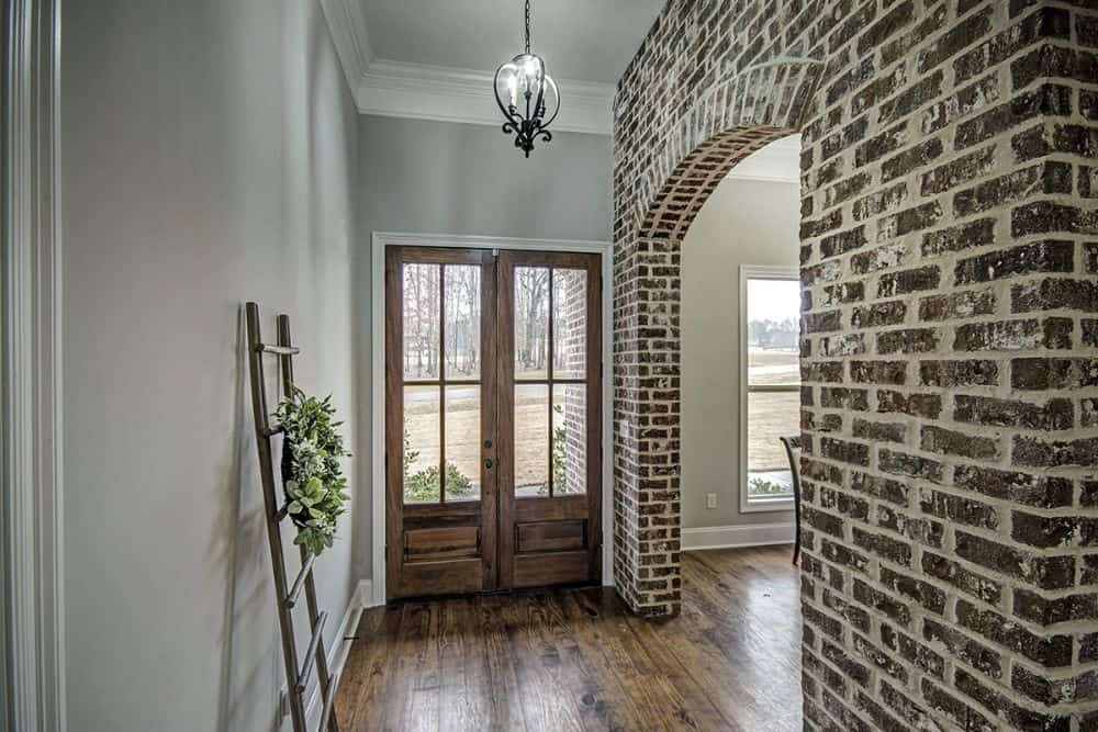 Foyer with a wooden ladder and a brick archway leading to the formal dining room.