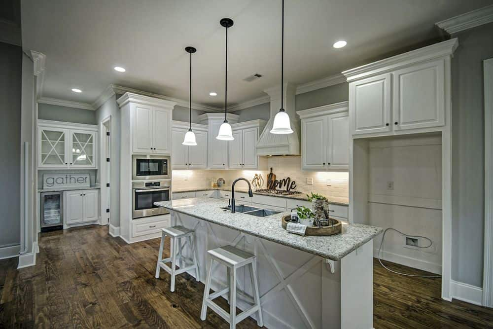 The kitchen offers white cabinetry, granite countertops, and a breakfast island paired with white bar stools.