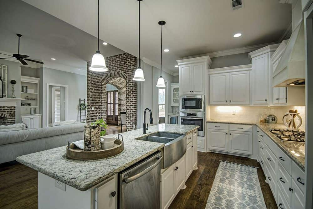 The breakfast island is fitted with a dishwasher, a double bowl sink, and a gooseneck faucet.