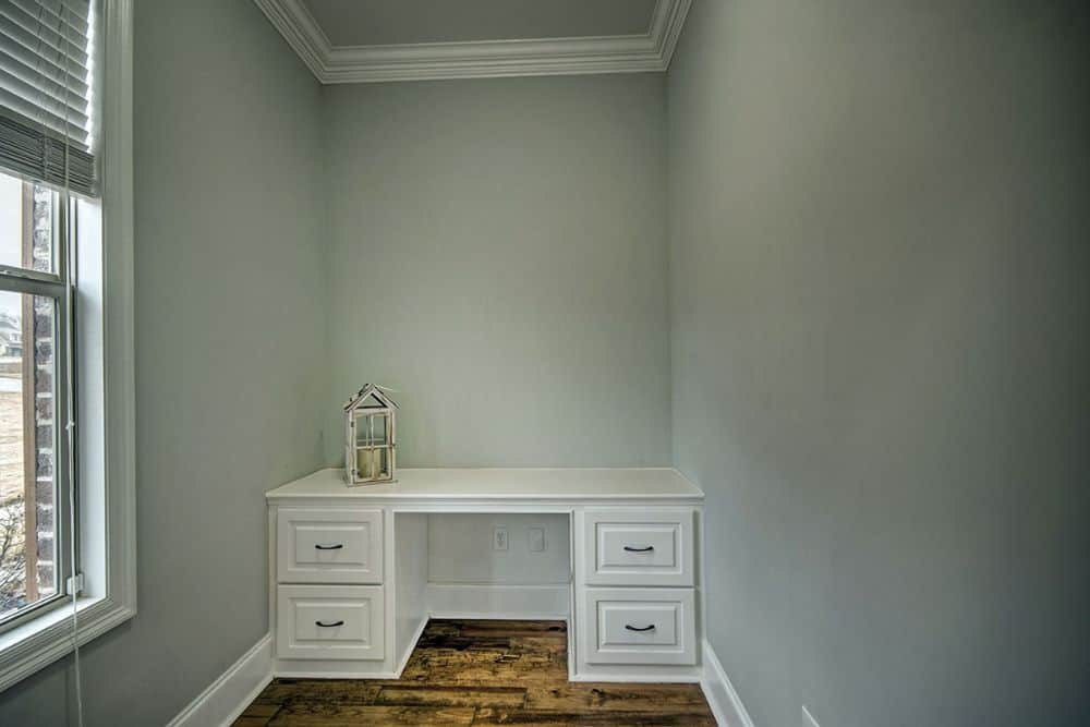 Study nook with gray walls and a white desk over the hardwood flooring.