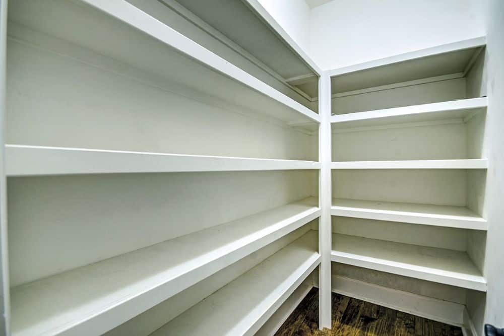 The walk-in pantry is filled with white built-in shelves.