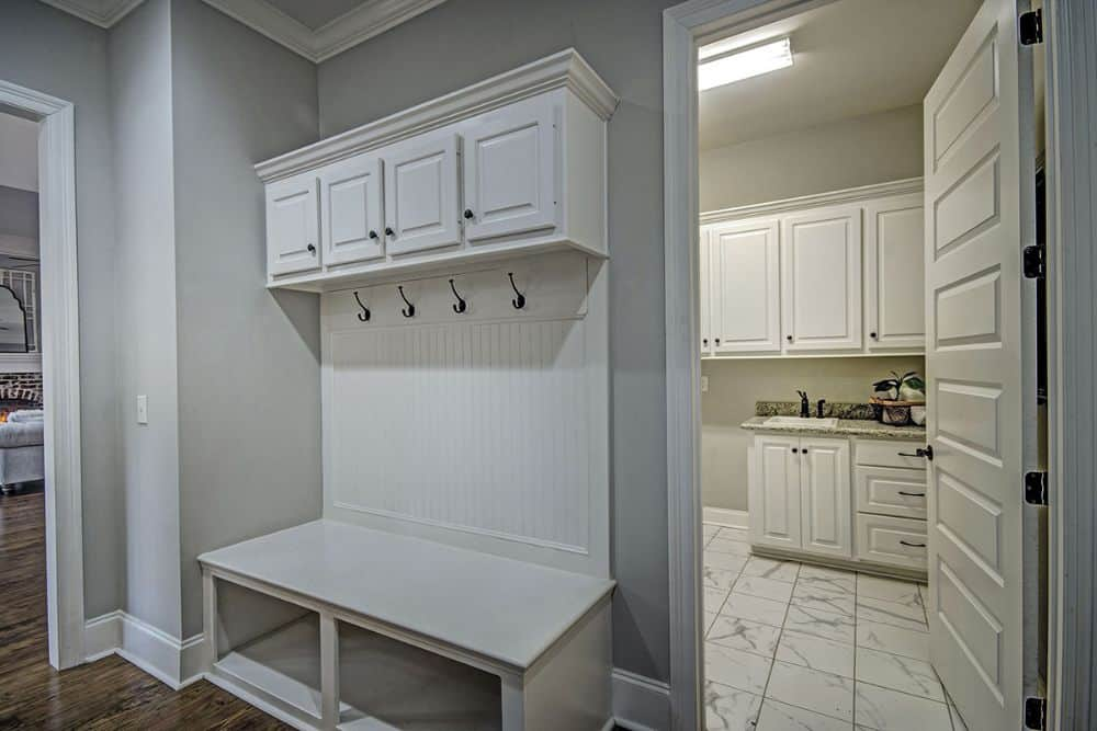 Mudroom with built-in storage and bench. A white door on its side opens to the utility room.