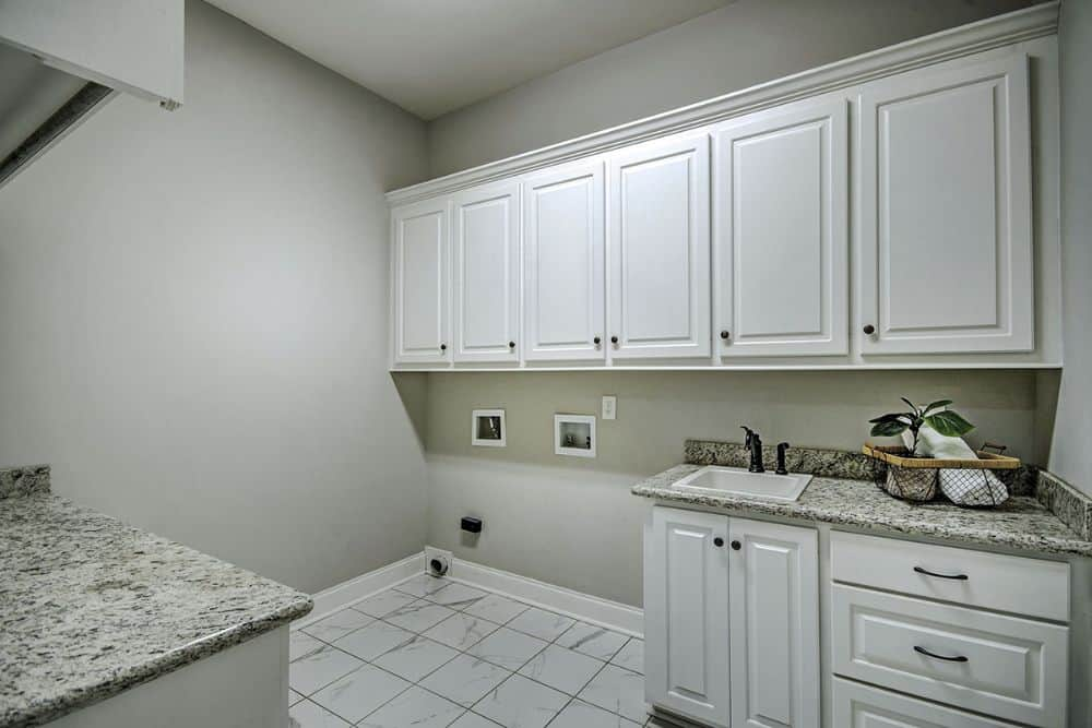 The utility room is equipped with granite countertops, a porcelain sink, and white cabinets.